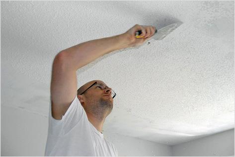 Мужчина снимает краску с потолка