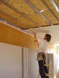 Мужчина занимается утеплением потолка