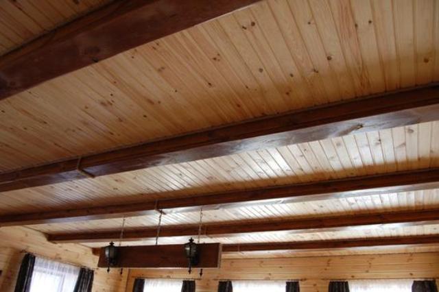 Деревянный потолок и сверху балки темно коричневого цвета